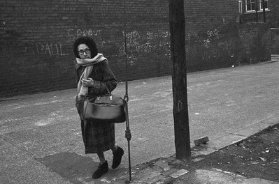 Woman walking by demolition, Byker, 1975