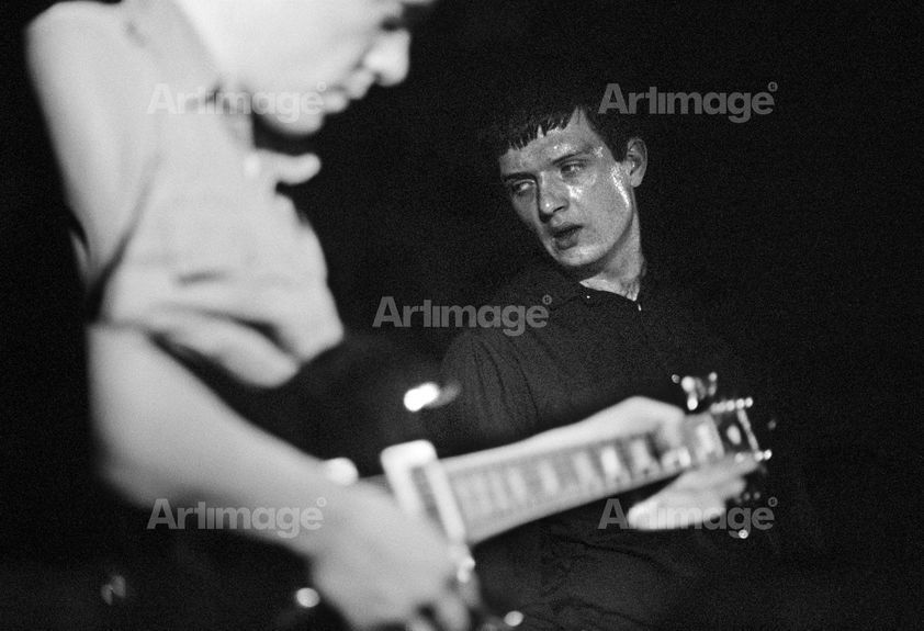 Enlarged version of Factory Records: Bernard Sumner and Ian Curtis of Joy Division, on stage, New Osbourne Club 'Factory' gig, Miles Platting, Manchester, 1980